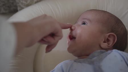 analık : Close up. Mother touches little sons nose who lying in his crib. Charming baby smile. Baby boy Stok Video