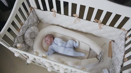невинный : Two-month baby boy in blue baby sliders is lying in the crib at home in bedroom. Baby boy trying to fall asleep in cot. Baby boy