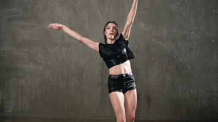 pirouette : Wet young woman dancer in black bodysuit is dancing emotional modern dance under the drops of water in the studio in front of the studio light. Training dancer dancing under water droplets