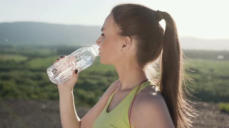 občerstvení : Fitness young woman drinking water from sport bottle. Cold drink after running training outdoor in mountain. Fit girl drinking water after fitness workout outdoor in sunset Dostupné videozáznamy