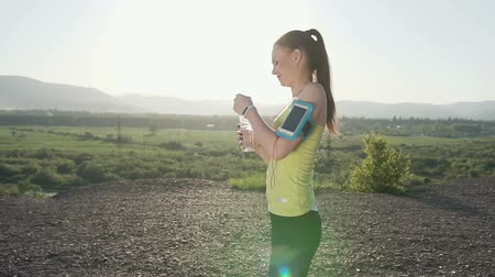 persone : Attractive female runner in the top of mountain gets her breath back and drinks water in slow motion. Summer rest of young sporty woman who drinking water from a bottle she is tired and relaxin Stock Footage