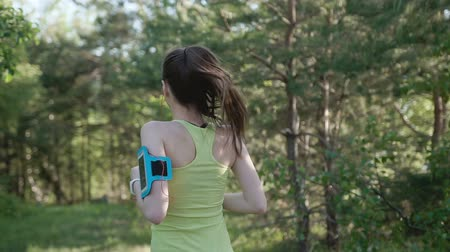 corredor : Rear view. Runner young woman running in park exercising outdoors fitness tracker wearable technology. Athletic girl training outdoor in the park