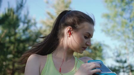 persone : Runner young woman running and exercising outdoors with fitness tracker and running app wearable technology with smart phone and earphones. Fitness girl with a smartphone, enjoys sports training, nature workout and listening music Stock Footage