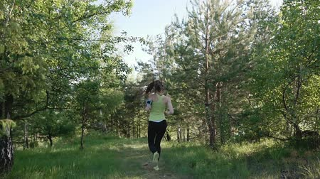 persone : Rear view. Runner young woman running in park exercising outdoors fitness tracker wearable technology. Athlete girl jogging in park she running from the camera and listen to music in headphone on a smartfone Stock Footage