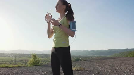 hidratar : Caucasian young woman drinking water from a bottle on top of a mountain for relax. A tired athlete rest for recovery active sport after be tired workout cardio. Healthy lifestyle Stock Footage