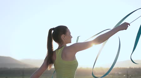 backflip : Close up. Attractive female gymnast dancing with blue ribbon in outdoors at sunrise or sunset. Slim gymnast in green body performs the gymnastics exercise with a blue ribbon on the nature Stock Footage