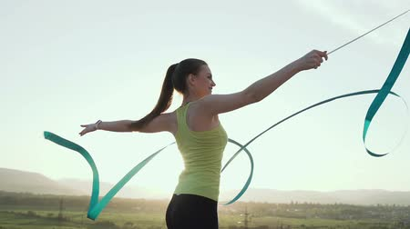 backflip : Rhythmic gymnastics: Girl in sport bodysuit perform gymnastics exercise with a blue ribbon on outdoor at sunset or sunrise. Gymnastic workout