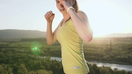 duruş : Close up. Beautiful kick boxing girl training on the top of mountain on sunset or sunrise at summer. Angry young woman doing boxing and looking on the camera. Beautiful female boxer training on the ourdoors in the morning Stok Video