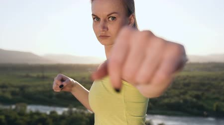 duruş : Close up. Angry kick boxing girl perform training on the top of mountain on sunset or sunrise at summer. Young woman doing boxing and looking on the camera. Beautiful female boxer training on the ourdoors in the morning