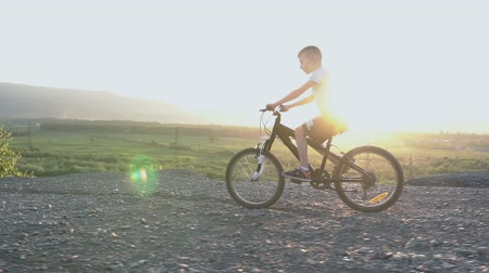 bisikletçi : Little kid riding bike in summer top of mountain at beautiful sunset sky background. Beautiful caucasian small boy of 8 years riding on bicycle in mountainous area over river on sunrise or sunset