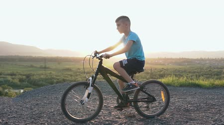 Орегон : A beautiful little boy who rides a black bike in a mountainous place in the summer in the east or in the sun. The child is cycling on top of a mountain over the river Стоковые видеозаписи