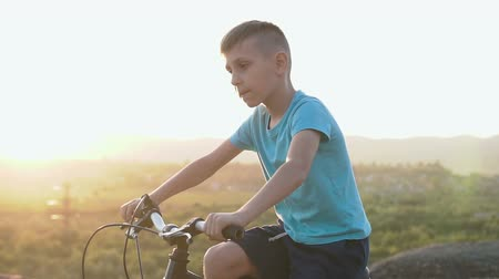 mães : A handsome boy 8-9 old in a blue T-shirt rides a bike in a mountainous area against the background of the forest in the sunset or sunrise. A child riding a sporty black bicycle at the dawn at summer Stock Footage