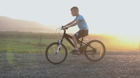 bisikletçi : 8-9 year boy in blue T-shirt who rides a black bike in a mountainous place at the summer in the sunset or in the sunrise. The child riding his bicycle on the stone road above the river
