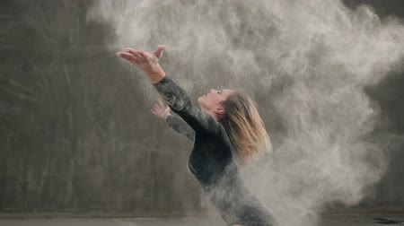 surrealismo : The dancer girl dressed in black body suit perform the contemporary dance on the floor, makes the stroke with the hair, raising a cloud of dust or white powder at indoors. Dance with white pigments