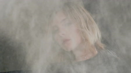 persone : Portrait of a girl with flying white powder or dust. Attractive young woman who dancing in a cloud of smoke or white powder at studio Stock Footage
