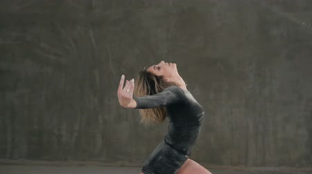 persone : A dancer dressed in black body suit perform a modern dance in a cloud of white powder or smoke against a background of a gray wall in the studio. Female ballet dancer perform on stage in theater Stock Footage