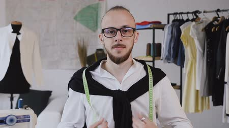 гордый : Close Up of smiling young fashion designer wearing eyeglasses. Portrait of happy guy with eyeglasses looking at camera. Close up of a joyful man with beard in glasses looking at camera