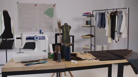 centímetro : A stylish studio for sewing clothes which has it sewing machine, coil threads, various sewing Items and fabrics laying around, mannequins standing and Sketches Pinned to the Wall, clothes on hangers and everything you need for sewing
