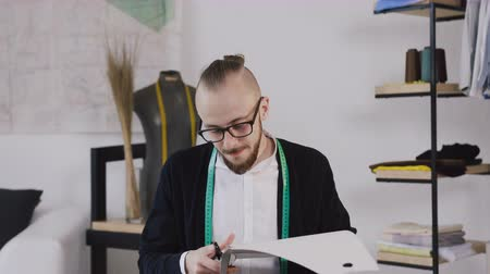 measure tape : A young designer or tailor sitting at a working sewing table at the studio and carving out with scissors a sketches for sewing a new collection. A stylish bearded fashion designer works in a studio behind the sewing table Stock Footage