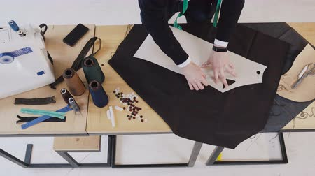 couturier : Top view of fashion designer or tailor making a pattern on a brown piece of tissue. Dressmaker is using a chalk, holding the sketch on textile