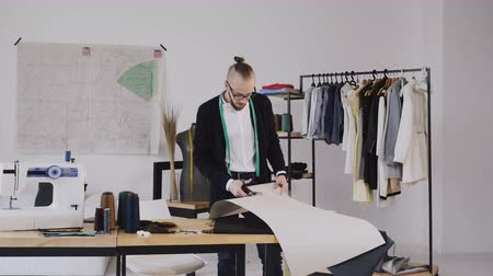 makas : Young male designer with tape-line on his neck standing in dressmaking studio and cut with scissors a pattern for a new collection. Male bearded fashion designer and tailor in atelier cutting out a pattern for future clothes Stok Video