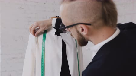 measure tape : Portrait of a tailor while making a white jacket using the tape measure. Close-up of a professional caucasian tailor taking measures with measuring line on mannequin while crafting a new fashion collection Stock Footage