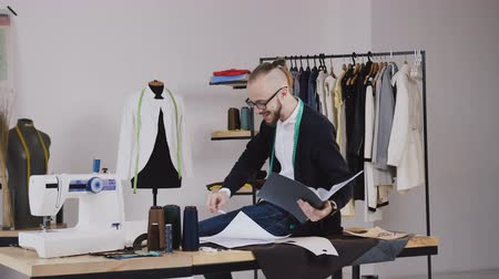 závit : Handsome fashion designer sitting on table in atelier and holds a folder with sketches, he makes notes in his notebook. Young bearded tailor in glasses dressed in white shirt and black blouse with measure tape on neck working in atelier Dostupné videozáznamy
