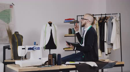 závit : A handsome fashion designer sits on the table in the studio and draws sketches for tailoring the new collection of clothes. A young bearded tailor wearing glasses, dressed in a white shirt and a black blouse with a measuring handle on his neck, working in
