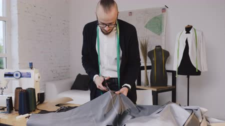 makas : Handsome tailor cutting fabric using large scissors or shears as he follows the chalk markings of the pattern Stok Video