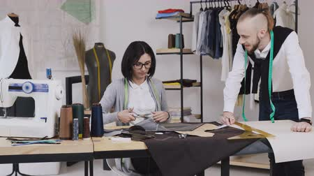 makas : Team work of two tailor and dressmaker who are smile and working on sewing a new collection. The seamstress cuts pattern with scissors and the stylist follows the workflow Stok Video