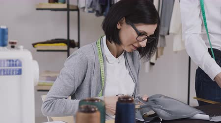 designing : Close-up of a dressmaker that sits at the table and cuts gray material with scissors for sewing clothes in a small stylish atelier. Young woman tailor working with scissors at the studio with different tailoring tools and clothes Stock Footage
