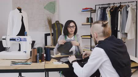 портной : Young woman and man fashion designers or tailors working with gray fabrics sitting at the beautiful office with different tailoring tools on the table. Two people fashion designers choosing fabric at the office with different tailoring tools and clothes
