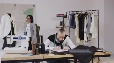 odlišný : Two fashion designers working at the office with different tailoring tools sand clothes. Working on new collection together. Caucasian fashion designer and tailor