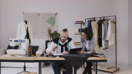 centímetro : Fashion designers working at the office with different tailoring tools and clothes. Two fashion designers man and woman discuss design new collection