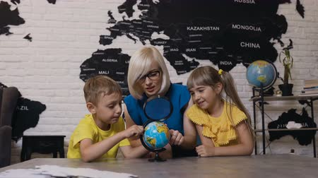 mladistvý : Teacher with two kids in geography class looking at globe. Cute boy, girl and teacher looking at the globe using magnifying glass in the classroom at school or kindergarten
