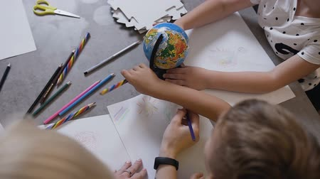 kreslit : Top view. At the drawing lesson, the children sit at the table and draw with the teacher. Children paint with pencils. Pupils with teacher draw on white paper with crayons Dostupné videozáznamy