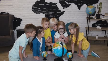 nagyító : Little caucasian students of boys and girls looks at globe while listening to teacher on the geography lesson. One of the girls looks at the globe through the magnifying glass