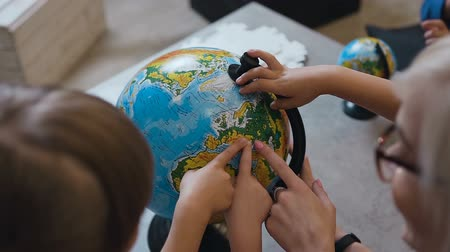 pertavsız : Top view. A blonde woman discussing over a globe with the kids at indoors. Teacher with pupils who discussing over a globe at on geography lesson at school Stok Video