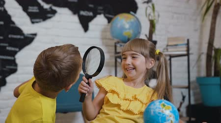 estudioso : Portrait of the lovely two pupils who with fun study the globe with a magnifying glass in her hands in classroom. At the lesson of geography or history Stock Footage
