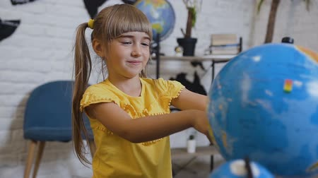 senta : A sweet girl in a yellow T-shirt sits at the table in the classroom of geography and is curiously studying the globe or world map. Girl of 6 years twists the globe or world map and studies the world