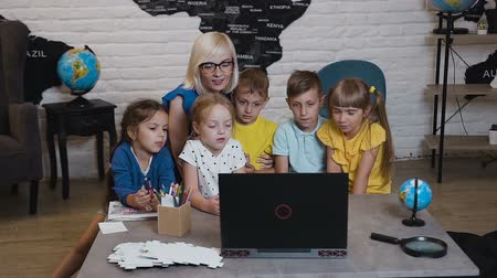 ter cuidado : Happy teacher using laptop with pupils in the classroom of geography. Teacher helping caucasian children learning at laptop in primary school