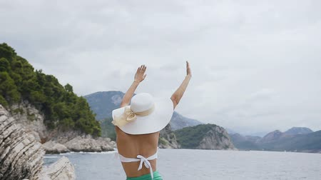 купание : Back view. Slim tanned girl dressed in white-green swimsuit with big hat, standing on a cliff, raising her arms up and admiring landscapes and the sea. Girl with raised hands standing by the sea