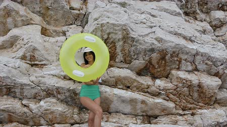 skalnatý : Slim beautiful brunette in a green swimsuit and a big hat smiles at the camera through the inflatable yellow float or circle at the rock background. Tanned young woman with inflatable float