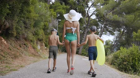 nafukovací : Back view. A young woman in a swimsuit and a large hat with two children go from the beach to the park. Two son and their mother are walking in the park near the adriatic sea