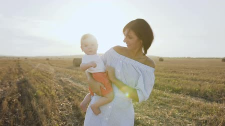 hay fields : Portrait of happy caucasian mother who holds her little son, she playing with the baby in the field at sunset. Happy young woman playing with little son in the field with bales at sunset Stock Footage