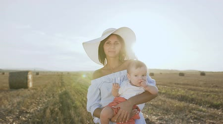 saman : Portrait of a beautiful young woman in a dress with a big hat and her little son in a white body standing in a golden field with bales in the sunset. Warm autumn, harvest, field, bales of straw