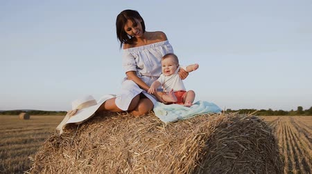 szénaboglya : Young mother with her baby boy playing sitting on a haystack in the field at sunset. A woman and her son are sits in the outdoors of the field on the hay bales