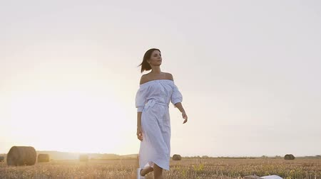 saman : A young girl running in the field makes circles around him on a summer evening at sunset. Attractive girl in a long dress goes a trail on the field with bales of straw Stok Video