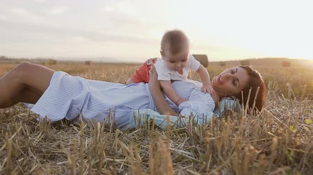 szénaboglya : Young woman with her adorable 6 month boy playing outdoors in the field. A young mother holding a small son on her arms lays in the field in the summer in the sunset Stock mozgókép