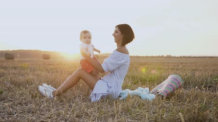 szénaboglya : A young woman in a light dress is sitting on the grass in the field and plays with a lovely baby. Happy mother with son walks in the field in summer evening. Straw bales in the field. Stock mozgókép